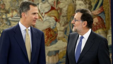 King Felipe talks with Spain's now acting Prime Minister Mariano Rajoy at the Zarzuela Palace in Madrid on Tuesday.