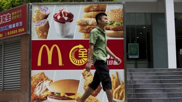 A pedestrian walks past an advertisement for McDonald's in the Futian district of Shenzhen, China, where sales have been hit hard after a McDonald's supplier was accused of repackaging old meat.