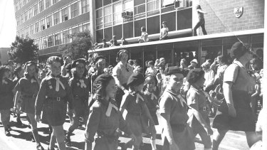 A parade of Guides and Brownies in Canberra in 1964. Note the casual OH and S vibe at the time as kids scramble on to rooftops to watch the passing parade.
