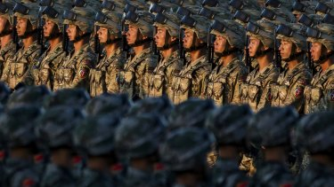Chinese soldiers march past Tiananmen Square.