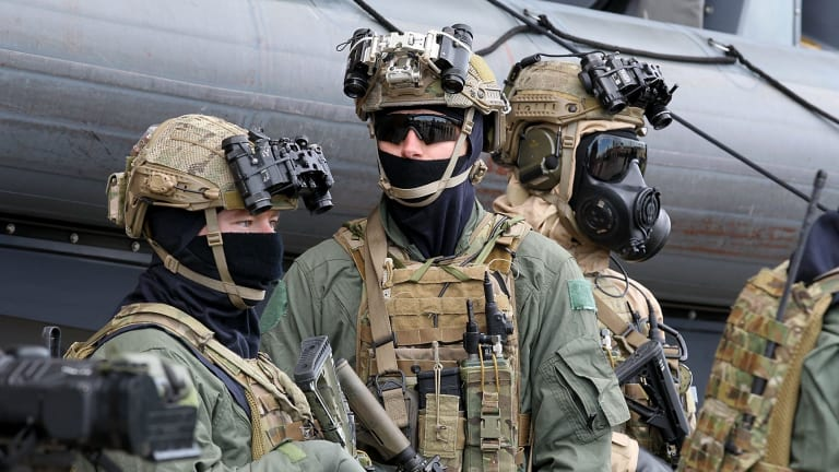 Armed and masked special forces troops at the announcement of the government's new policies on military involvement in terrorist incidents.