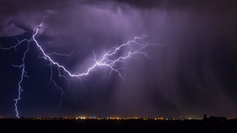 A woman has died and a man remains in hospital after being struck by lightning.