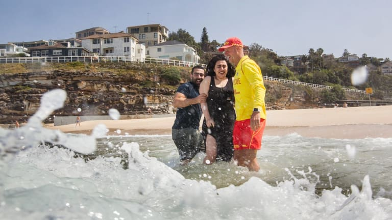 Volunteer lifesaver Paul Borrud talks to new Syrian migrants Alaa (Alan) Alnseer and his sister Lama at a beach safety day for new migrants at Tamarama.