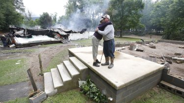 Jimmy Scott gets a hug from Anna May Watson, left, as they clean up from severe flooding in White Sulphur Springs, West Virginia. Scott lost his home to the flood and a fire that consumed his and the homes of several relatives.