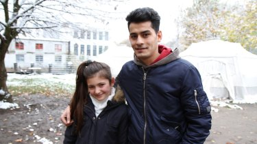 Yazidi refugee Renda Barakat, 11, with Majid Dhalriaiyam, 17, from Afghanistan outside a snow-covered refugee shelter in Germany.