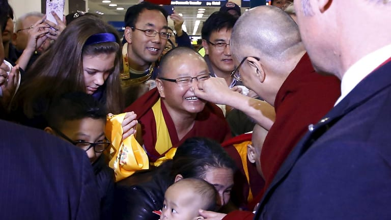 Exiled Tibetan spiritual leader the Dalai Lama pinches the nose of a supporter after arriving in Sydney on Thursday.