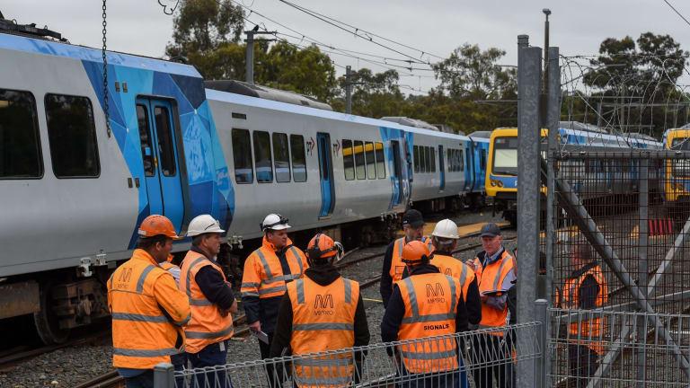 Rail workers survey the damage after the derailment.