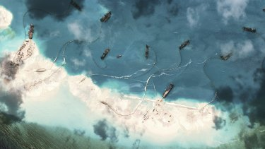 A handout satellite image shows dredgers working at the northernmost reclamation site of Mischief Reef, part of the Spratly Islands, in the South China Sea, March 17, 2015.