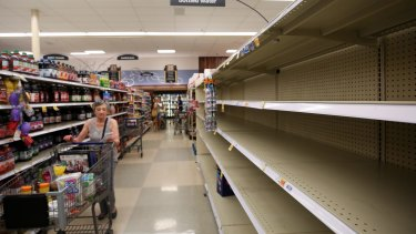 A shopper finds empty shelves on the bottled water section of a grocery store on in preparation of Hurricane Harvey in Houston.