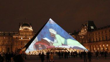 Pictures are screened on the pyramid of the Louvre museum in Paris, as part of the launch of the Louvre Abhu Dhabi.