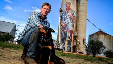 Local sheep and wheat farmer Nick Hulland, who is depicted on the disused silos at Patchewollock, in the Mallee, with his dog Wally.