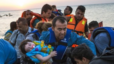 A man carries a girl in his arm as they arrive with other migrants just after dawn on a dinghy after crossing from Turkey to the island of Kos in southeastern Greece.