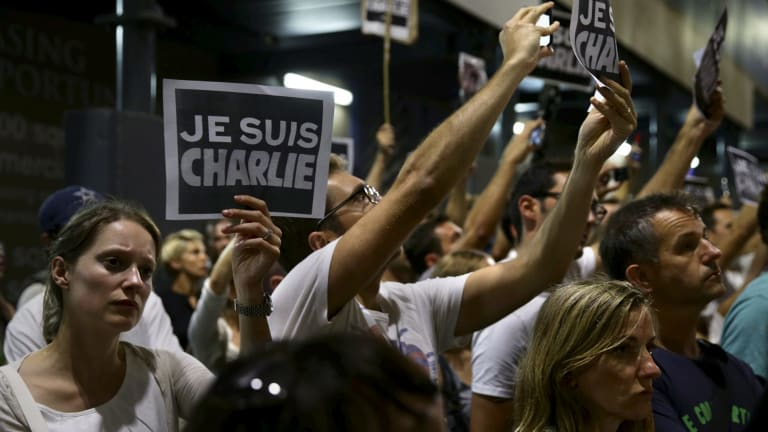 "The mourners held up signs saying ""Je suis Charlie"", which translates to ""We are Charlie""."