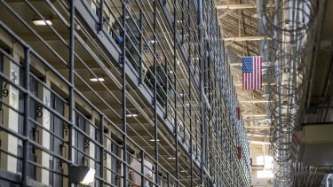 An inmate walks to his cell as corrections officers patrol at San Quentin Prison.