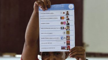 An election worker holds up a ballot during the presidential election's vote counting at a polling station in Dili, East Timor.