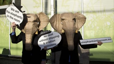 Representatives of NGOs wear elephant masks and hold banners at the United Nations Climate Change Conference in Paris.
