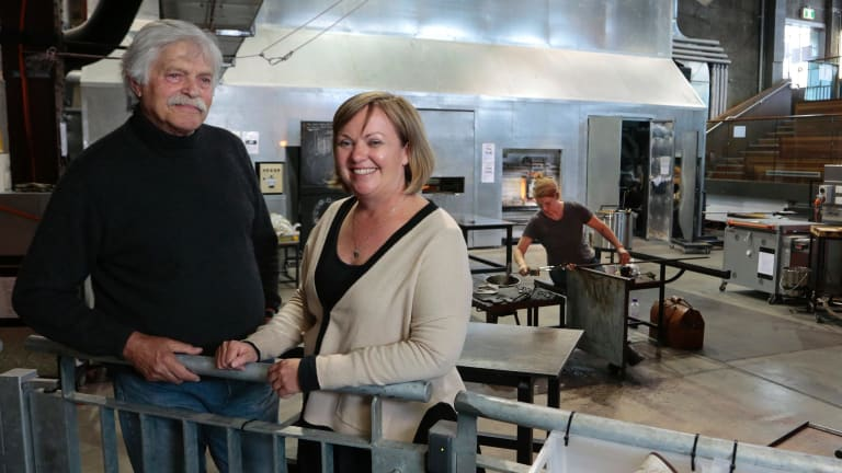 Canberra Glassworks founder Klaus Moje with general manager Beverly Growden as artist Sophia Emmett works in the hotshop.