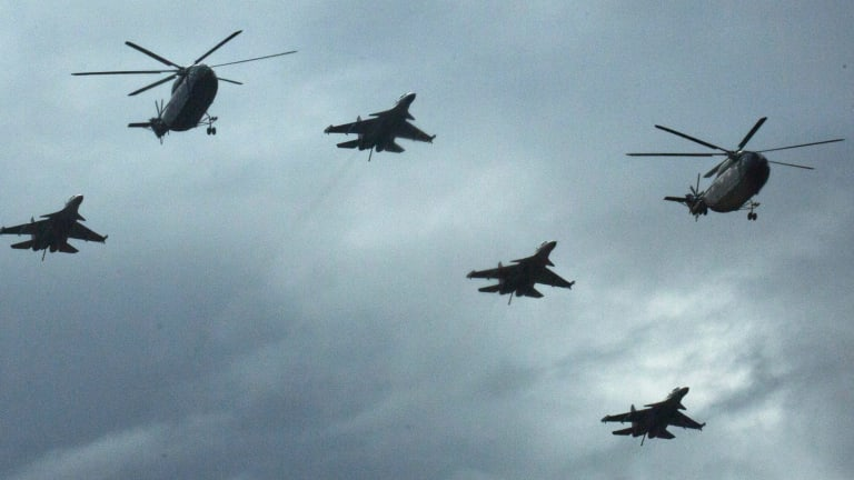 Military helicopters and fighter jets rehearse overhead.