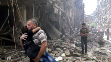 A man carries a child after airstrikes hit Aleppo on Thursday.