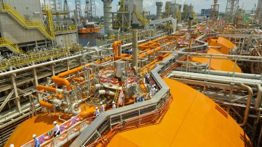Crew members walk on board a floating liquefaction vessel built by Keppel Offshore and Marine.