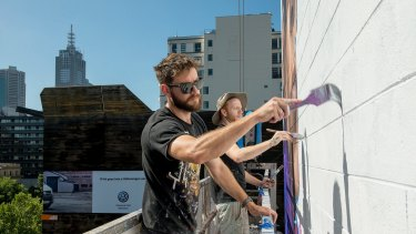 Artists Jason Parker and James Dewing  work on the Zoolander 2 mural.