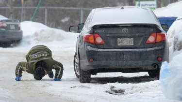 A police officer looks for evidence under a car in the area of a Quebec City mosque.