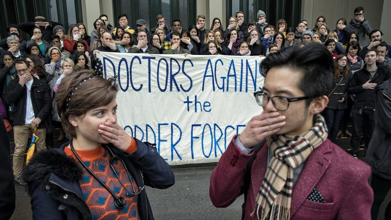 A group called Doctors Against the Border Force Act hold a silent protest at Carlton Gardens on Saturday.