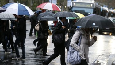 Commuters brave the rain in Sydney on Monday.