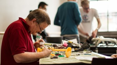We'll have a go: Volunteer Daryl Maunder mends a broken toy at the free Melbourne Repair Cafe in Yarraville.