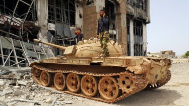 Libyan pro-government forces stand on a tank in Benghazi, Libya. The country is close to anarchy and is now IS' third biggest stronghold.