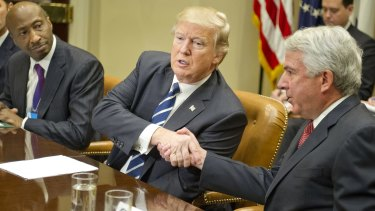 US President Donald Trump shakes hands with Robert Hugin, chairman of Celgene Corporation, alongside Merck CEO Ken Frazier (left) during a meeting with pharmaceutical company representatives at the White House in January.