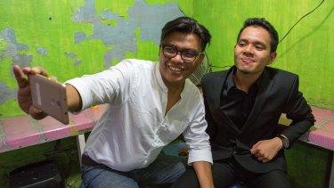 Filmmaker Noor Huda Ismail (left) and student Teuku Akbar Maulana take a selfie using a smartphone in Jakarta.
