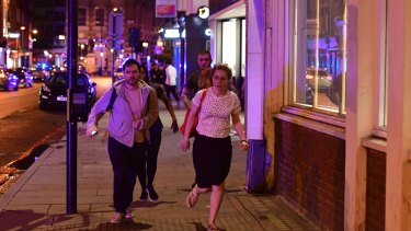 """People run down Borough High Street as police deal with a """"major incident"""" at London Bridge."""