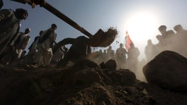 Afghan men bury a victim of Friday night's suicide attack at the Shiite mosque.