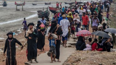 Rohingya Muslims, who crossed over from Myanmar into Bangladesh, walk towards the nearest refugee camp at Teknaf.