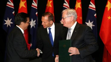 Prime Minister Tony Abbott and Minister for Trade Andrew Robb shake hands with China's Minister of Commerce, Gao Hucheng, during the China-Australia FTA signing ceremony in Canberra last week.
