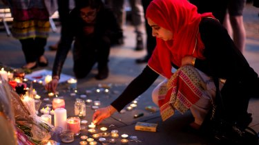 Female solidarity: A woman lights candles after a vigil in Albert Square, Manchester.