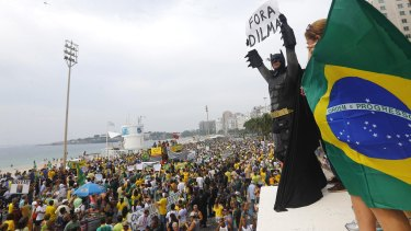 """An anti-government demonstrator dressed as Batman holds a placard reading """"Out Dilma"""" during a protest against Brazil's President Dilma Rousseff on Copacabana beach in Rio de Janeiro earlier this month."""