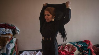 Zahra Yaganah, an activist, writer and mother of two teenagers, puts on her headscarf before she goes to work in Kabul.
