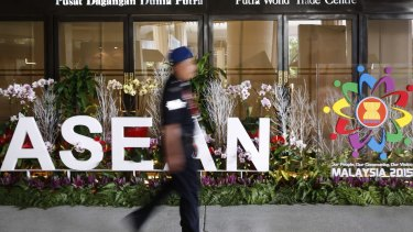 A Malaysian police officer walks past an ASEAN logo during the 48th ASEAN Foreign Minister Meeting in Kuala Lumpur.