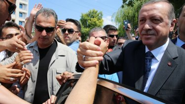 Turkey's President Recep Tayyip Erdogan shakes hands with supporters outside the Osmanli mosque in Ankara on Thursday.