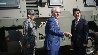 Australian Prime Minister Malcolm Turnbull, centre and Japanese counterpart Shinzo Abe at Narashino Exercise Area east of Tokyo on Thursday.