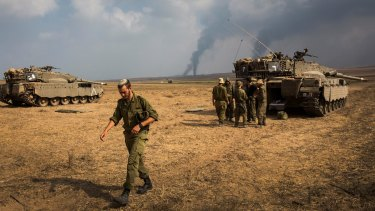 New threat: Israeli soldiers stand near their tank while smoke from air strikes and shelling rises from Gaza on July 22 near Sderot, Israel.