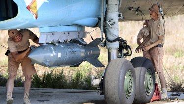 Russian military support crew attach a satellite-guided bomb to a jet fighter in Syria.