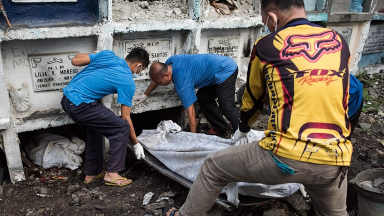 Morgue workers carry an unclaimed body and victim of an extrajudicial killing in Manila, Philippines last week.