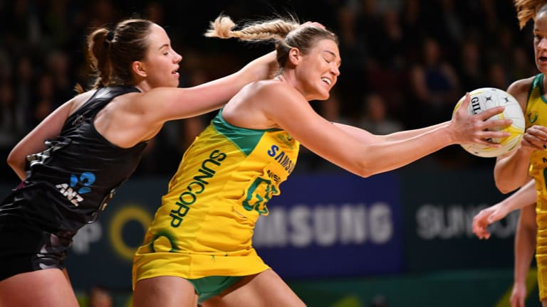 Caitlin Bassett of Australia and Kelly Jury of New Zealand fight for the ball.