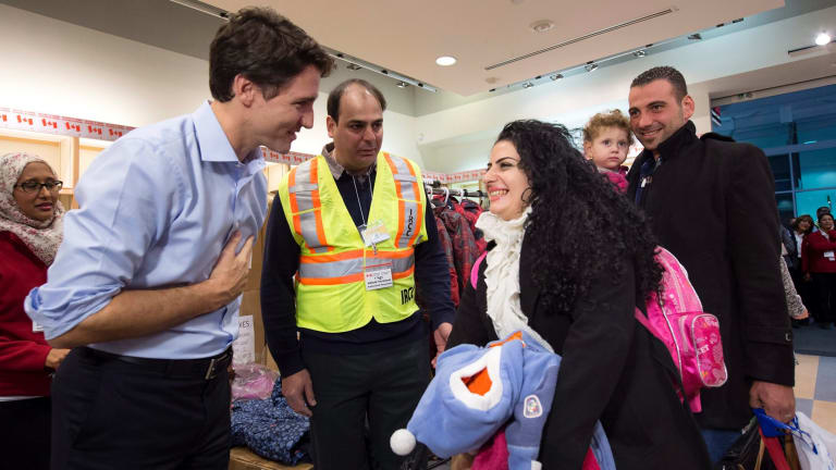 Prime Minister Justin Trudeau, left, greets Georgina Zires, center, Madeleine Jamkossia and her family, refugees fleeing from Syria, as they arrive at Pearson International airport, in Toronto on December 11, 2015.