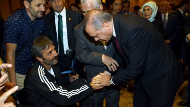 Mr Erdogan, right, shakes hands with a wounded civilian during an event to honour those killed and wounded during the failed coup.