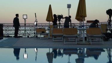 Television media doing a standup are reflected in a swimming pool at the media center during the G7 Taormina summit.