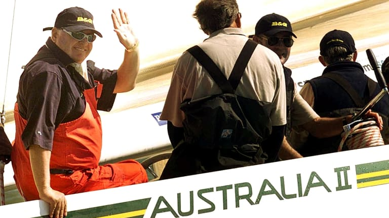 Australian entrepreneur Alan Bond waves from Australia II, during a race around the Isle of Wight, England in 2001 for the America's Cup Jubilee.